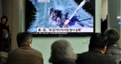 South Korean people watch a TV screen sh