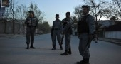 Afghan policemen stand near a building w