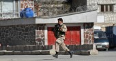 An Afghan security officer runs to a bui