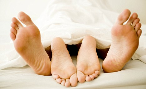 Young couple's feet under blanket
