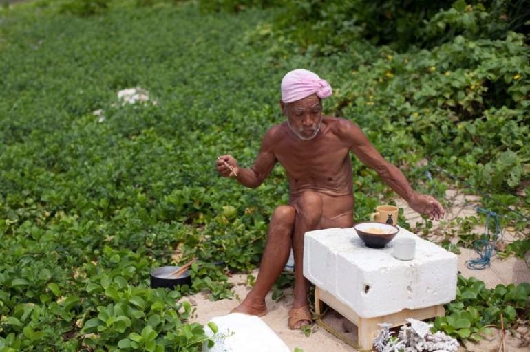 Seventy-six-year-old naked hermit Nagasaki eats a food on Sotobanari island, Okinawa prefecture, Japan