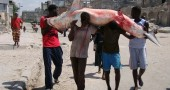 Somali fishermen carry a shark from the