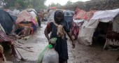 A Somali refugee walks past makeshift ho