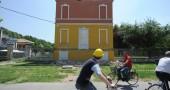 People ride past a school in Mirandola,