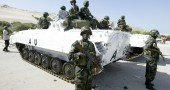Ugandan soldiers stand guard next to U.N. armoured personnel carrier in Mogadishu's international airport