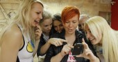 Activists of Ukrainian women's rights group Femen look at pictures on a mobile phone at their office in Kiev