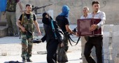 Syrian civilians carry their belongings