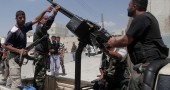 Syrian rebel fighters stand around an an
