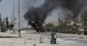 Syrians walk past a burning vehicle in t