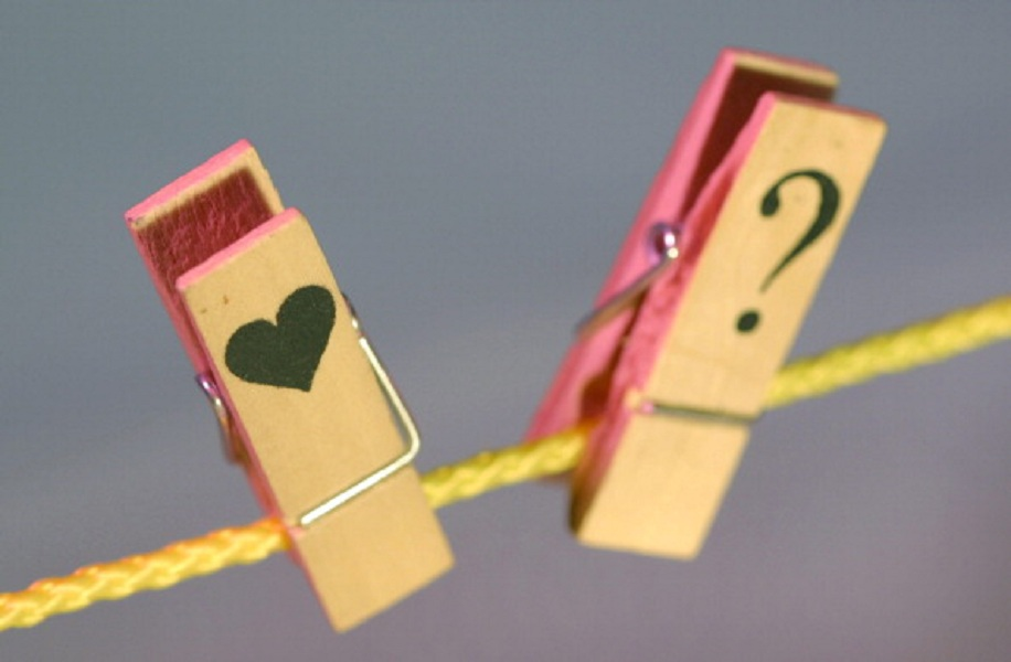 Two clothespins at a clothesline ( with heart and question mark ), Symbolic picture for: Love, seperation, relationship.