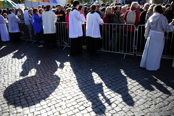 Priests hand out communion during a mass