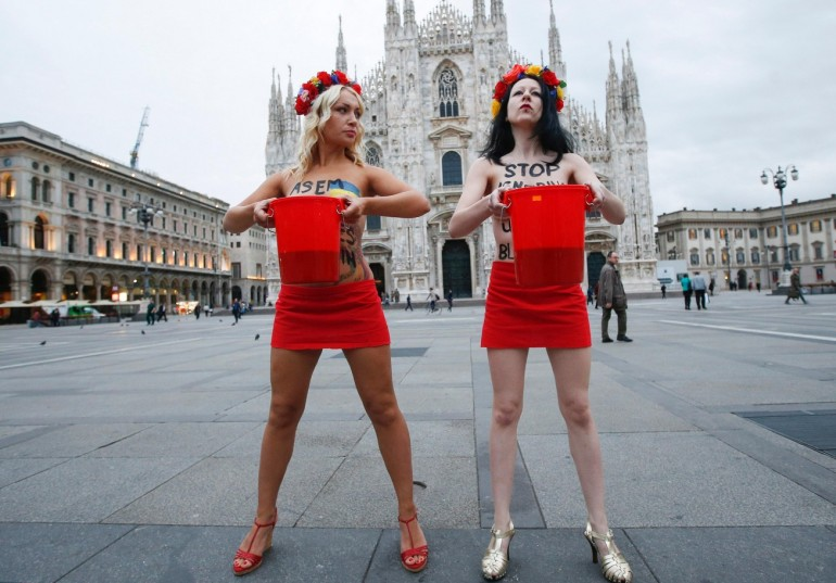 Inna Shevcehenko, leader delle femen (a sinistra) e un'altra attivista protestano in Piazza del Duomo (Photo credit MARCO BERTORELLO/AFP/Getty Images)