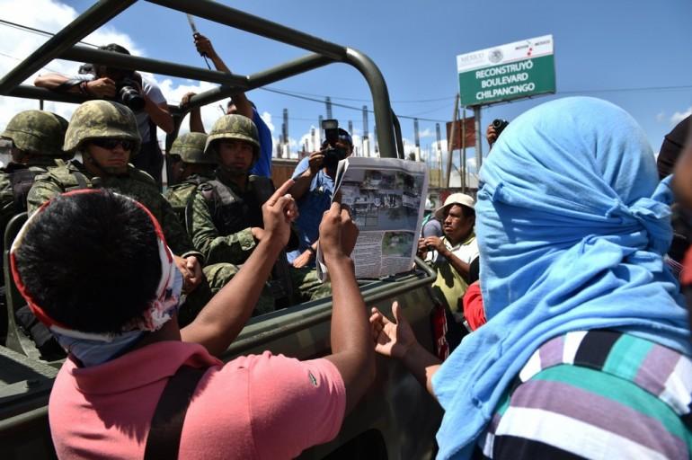 Studenti, prudentemente mascherati, protestano chiedendo giustizia per la strage di Iguala (Photo credit YURI CORTEZ/AFP/Getty Images)