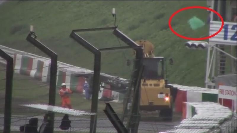 La bandiera verde sventolata dal commissario sulla torretta alla Dunlop Curve. Quattro secondi dopo la vettura di Bianchi finisce sotto il mezzo. Il commissario sventolerà ancora la bandiera verde per un minuto e cinque secondi prima che un collega salga sulla torretta