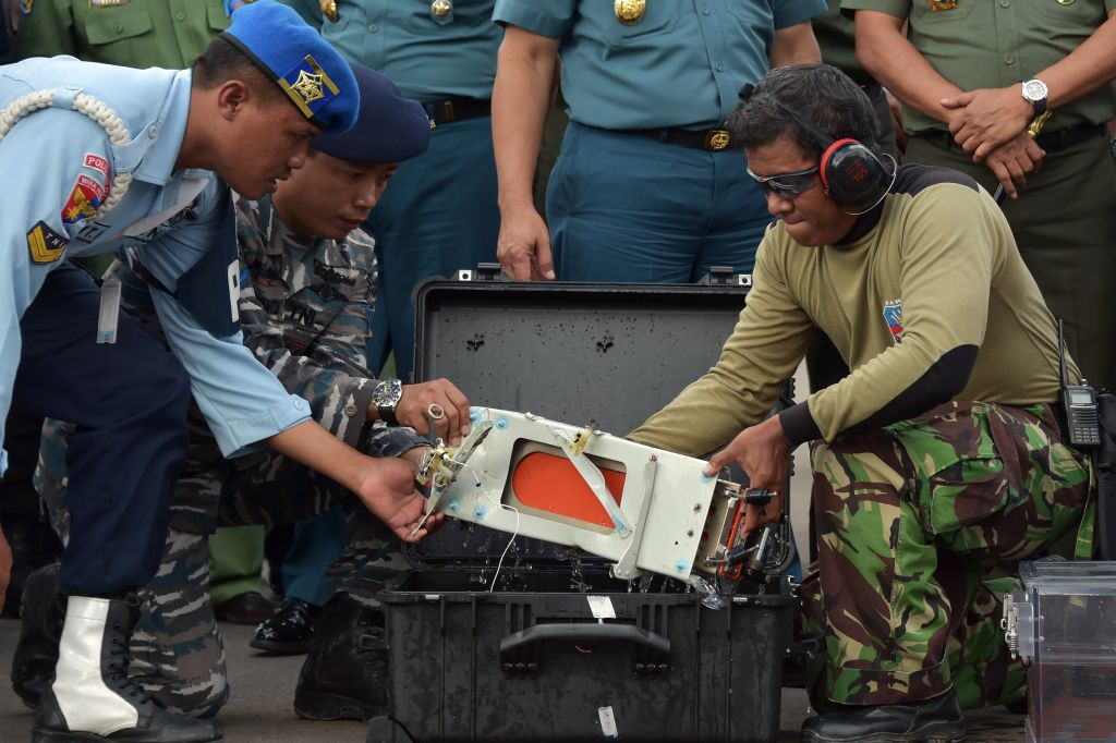 Gli esperti indonesiani mettono il FDR (Flight Data Recorder) del volo  AirAsia QZ8501 in un contenitore adatto al suo trasporto a terra  (Photo credit ADEK BERRY/AFP/Getty Images)