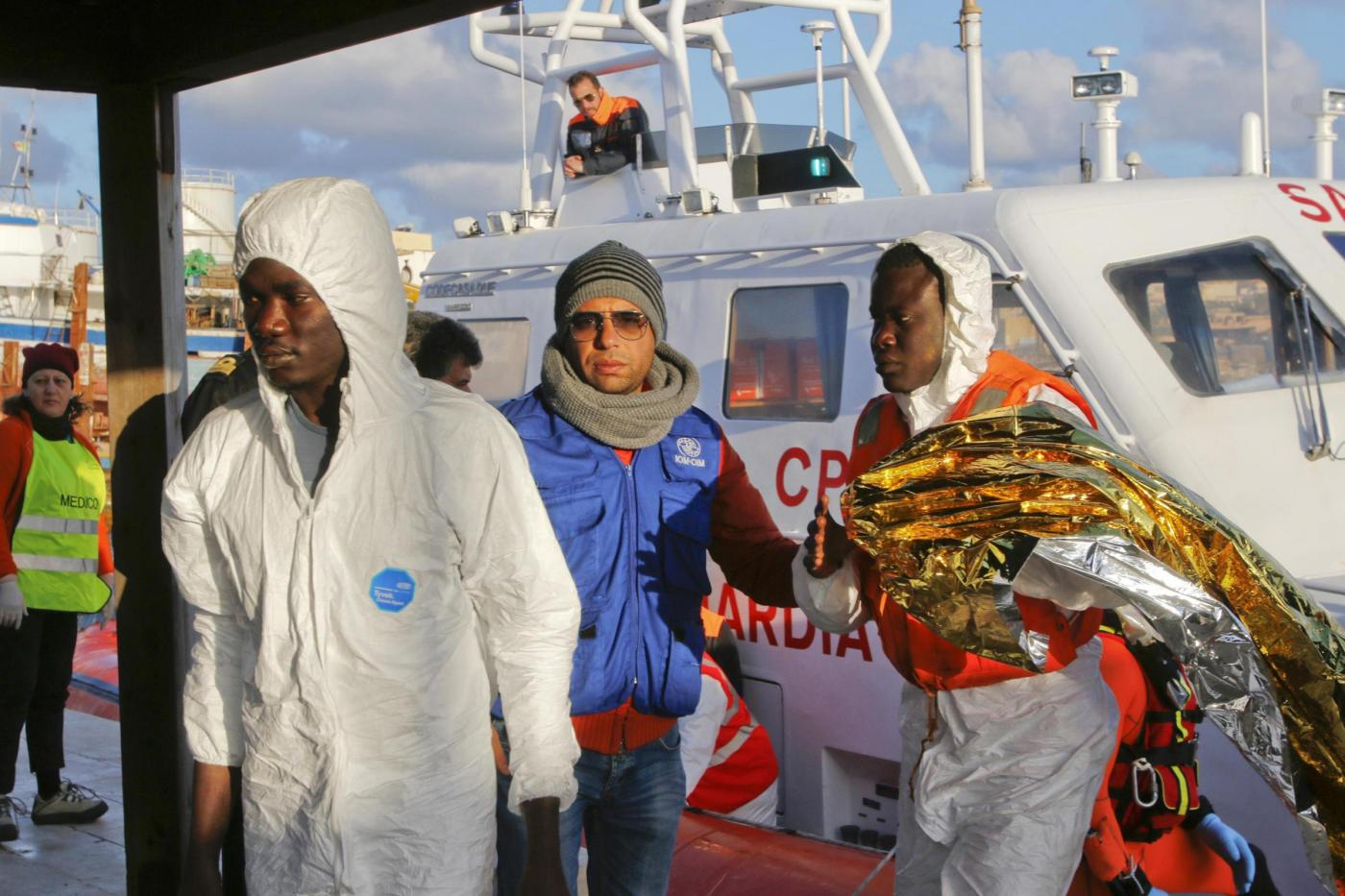 Migrants who survived a shipwreck are escorted as they arrive at the Lampedusa harbour
