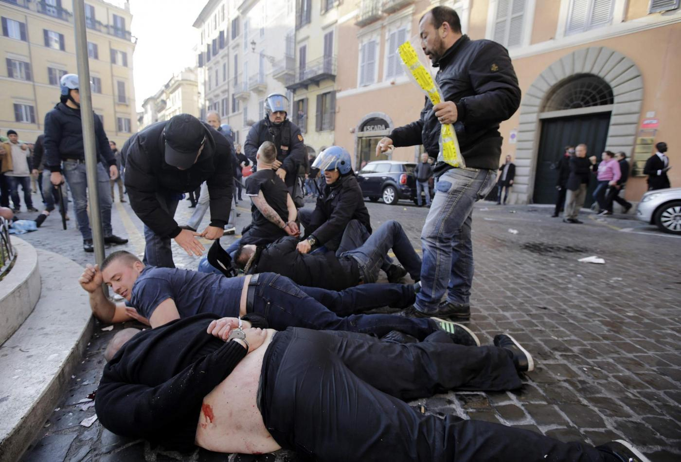 Feyenoord fans lie facedown on the street after being detained during clashes that broke out at the Spanish Steps prior to the start of the Europa League soccer match between Roma and Feyenoord in Rome