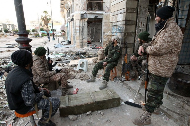 Libyan soldiers, loyal to Libya's internationally recognised government of Abdullah al-Thani and General Khalifa Haftar, rest on a sidewalk in the eastern coastal city of Benghazi on February 28, 2015. Benghazi is one of the less stable areas of the North African state, which has been plunged into chaos since the 2011 revolution that toppled dictator Moamer Kadhafi. AFP PHOTO / ABDULLAH DOMA (Photo credit should read ABDULLAH DOMA/AFP/Getty Images)