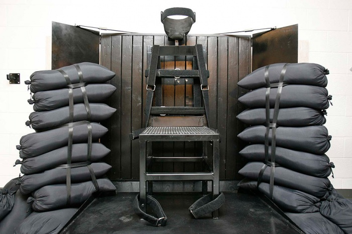 Death penalty statistics: the execution chamber at the Utah State Prison after Ronnie Lee Gardner was executed by firing squad Friday, June 18, 2010. The bullet holes are visible in the wood panel behind the chair. Photograph: Trent Nelson/AP