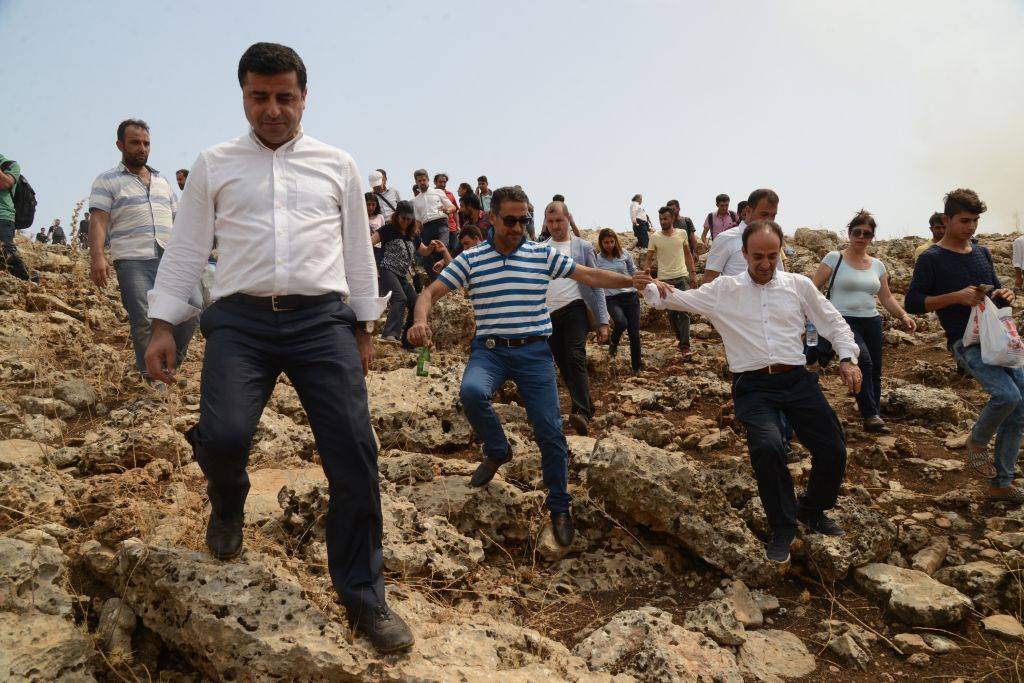 The leader of Turkey's main pro-Kurdish Peoples' Democratic Party (HDP) Selahattin Demirtas (L) and his delegation walks through a field after the road leading to Cizre was blocked by the Turkish security forces on September 10, 2015, in Sirnak. HDP co-chairman Selahattin Demirtas has been leading fellow deputies and dozens of supporters on a march to Cizre to end the curfew and draw attention to the plight of its 120,000 residents. AFP PHOTOS/ILYAS AKENGIN (Photo credit should read ILYAS AKENGIN/AFP/Getty Images)