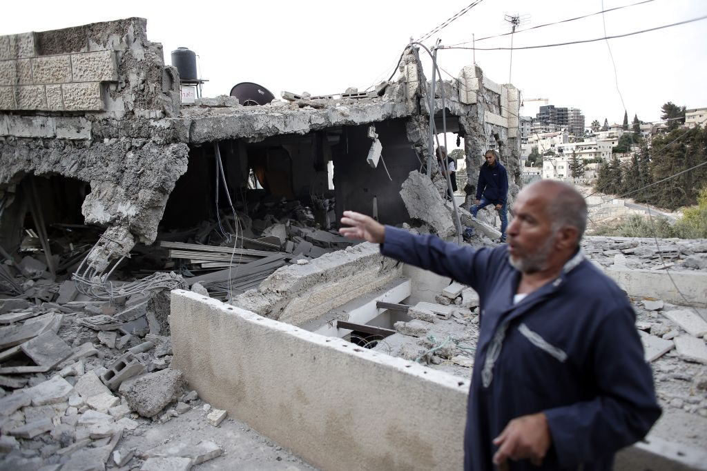 A Palestinian man shows the rubble of a destroyed house after Israeli security forces demolished the homes of two Palestinians behind attacks in the Palestinian neighborhood of Jabal Mukaber in east Jerusalem, on October 6, 2015. Israeli Prime Minister Benjamin Netanyahu pledged an iron fist against mounting unrest. The houses knocked down were the former homes of Ghassan Abu Jamal and Mohammed Jaabis, they killed four rabbis and a policeman before being shot dead in November 2014. AFP PHOTO / THOMAS COEX (Photo credit should read THOMAS COEX/AFP/Getty Images)