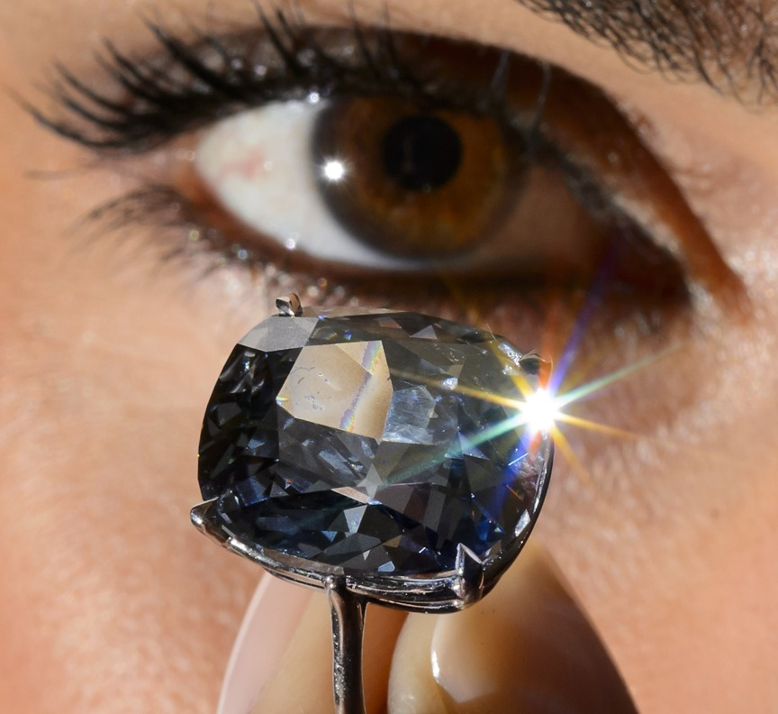A model poses with a 12.03-carat blue diamond during a press preview by auction house Sotheby's in Geneva on November 4, 2015. A 12.03-carat blue diamond could fetch a record $55 million (47 million Euros) when it goes under the hammer by Sotheby's on November 11 in Geneva. Categorised as a fancy vivid blue diamond, the Blue Moon, discovered in South Africa in January last year, is the largest cushion-shaped stone in that category to ever appear at auction. AFP PHOTO / FABRICE COFFRINI (Photo credit should read FABRICE COFFRINI/AFP/Getty Images)