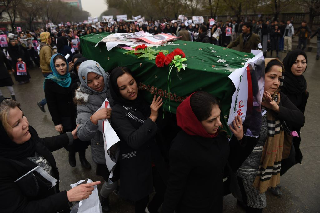 fghan protesters carry a coffin containing a decapitated body of one of seven Shiite Muslim Hazaras, including four men, two women and one child, during a demonstration in Kabul on November 11, 2015. Thousands of protesters marched coffins containing the decapitated bodies of seven Shiite Hazaras through the Afghan capital Kabul on November 11 to demand justice for the gruesome beheadings, which prompted fears of sectarian bloodshed in the war-torn country. Demonstrators gathered in the rain in west Kabul and marched towards the city centre, chanting death slogans to the Taliban and the Islamic State group while demanding justice and protection from the government. AFP PHOTO / SHAH Marai        (Photo credit should read SHAH MARAI/AFP/Getty Images)