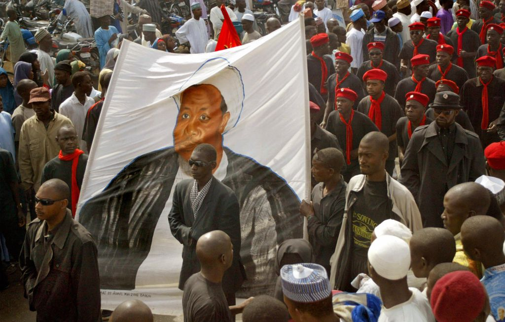 , NIGERIA:  Black-shirted followers of a hardline Shiite Muslim sect carry a banner depicting Ibrahim Zakzaky, a Nigerian Shiite radical who wants to set up an Islamic Republic, as thousands of Nigerian Muslims protest 10 February, 2005 in the northern city of Kano after weekly prayers on Friday to condemn cartoon drawings of the Prophet Mohammed published in European newspapers. Kano is often the scene of unrest and tensions in the sprawling trading centre have been further stoked by accusations from federal officials that the local state goverment is training a Jihadist militia. AFP PHOTO PIUS UTOMI EKPEI  (Photo credit should read PIUS UTOMI EKPEI/AFP/Getty Images)
